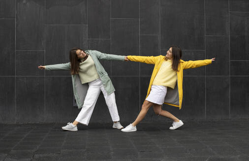 Sisters wearing blue and yellow raincoats holding hands while dancing on footpath - AXHF00015