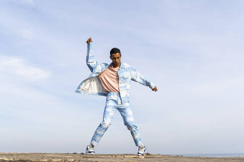 Man wearing denim suit dancing while standing against sky - AFVF08002