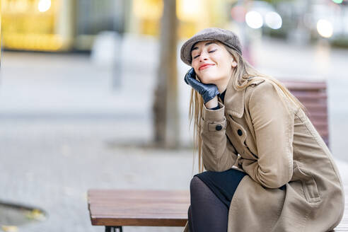 Smiling woman day dreaming while sitting on bench at footpath - GGGF00714