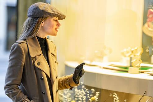 Caucasian woman doing window shopping at night - GGGF00717