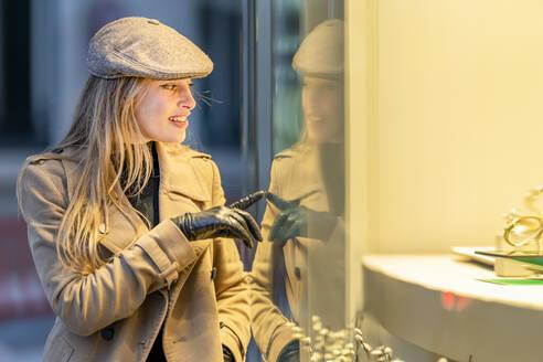 Beautiful woman doing window shopping at night - GGGF00720