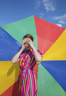 Woman shielding eyes while standing against colorful beach umbrella - AXHF00021