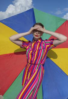 Beautiful woman shielding eyes against colorful beach umbrella - AXHF00024
