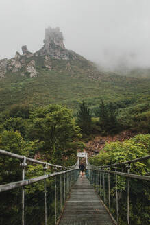 Mid adult woman walking on suspension bridge in forest - DMGF00430