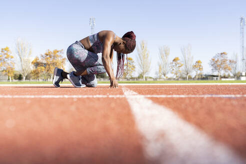 Female athlete in ready position on running track during sunny day - JCCMF00526