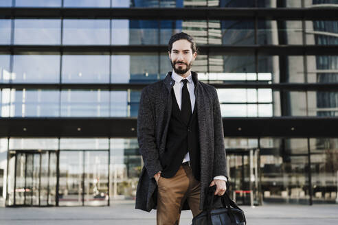 Male entrepreneur with hands in pocket carrying briefcase while standing against modern building - EBBF01996