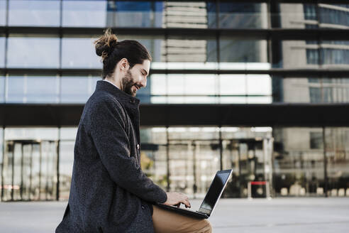 Young businessman working on laptop while sitting against building - EBBF01999