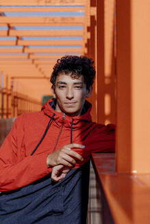 Confident young man leaning on orange railing - OGF00767