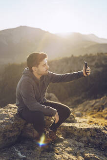 Young man taking selfie with smart phone while sitting on mountain during sunny day - RSGF00494