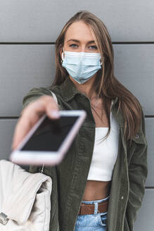 Young woman wearing face mask giving smart phone while standing against wall - JAQF00137