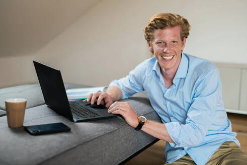 Smiling businessman with laptop by couch at home - MEF00091