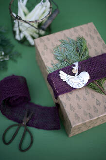 Christmas gift decorated with jute, fir twigs and pigeon shaped pendant - GISF00722