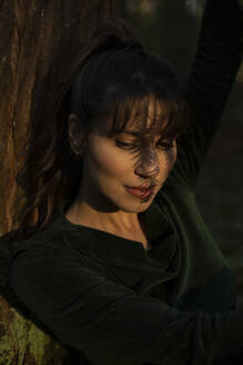 Woman looking down while shadow falling on face while leaning on tree trunk in sunlight - AXHF00028