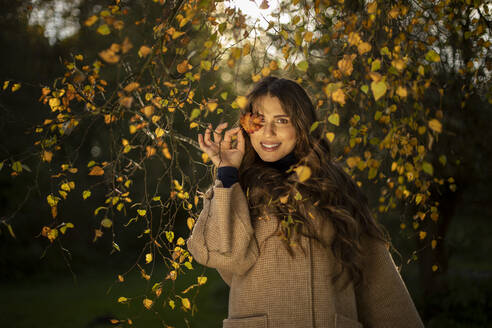 Smiling woman covering eye from autumn leaf in public park - AXHF00043