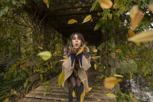 Cheerful woman blowing autumn leafs in public park - AXHF00046