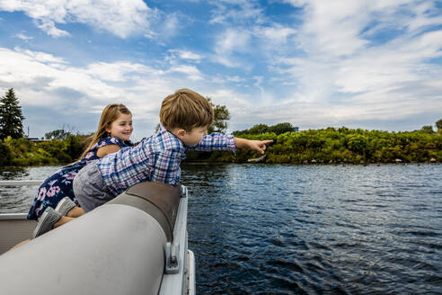 Boy pointing while enjoying with sister in boat on lake against sky - AWAF00029