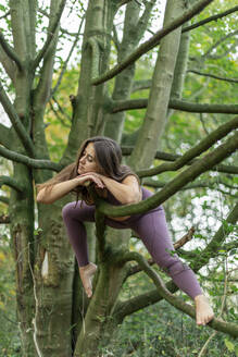 Young woman resting on branches in forest - AXHF00053