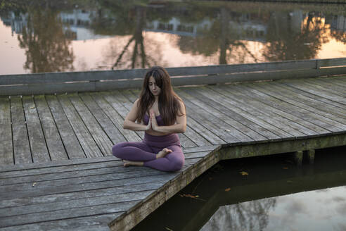 Woman with long hair meditating while sitting on pier over lake at sunset - AXHF00056