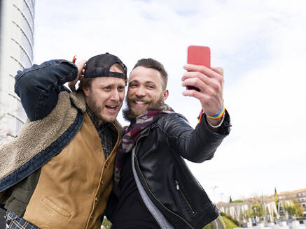 Cheerful man taking selfie with boyfriend while standing against sky - JCCMF00668