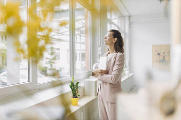 Businesswoman looking through window in office - GUSF04995
