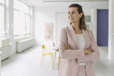 Smiling businesswoman standing in office - GUSF05001