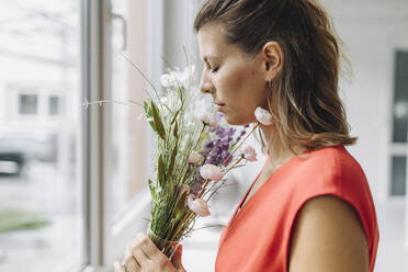 Woman smelling flowers at window - GUSF05007