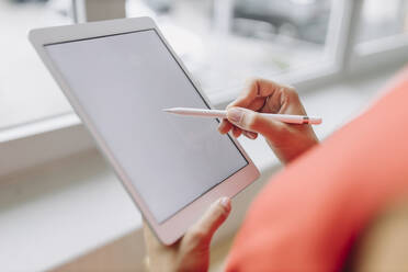 Businesswoman using digital tablet in office - GUSF05019