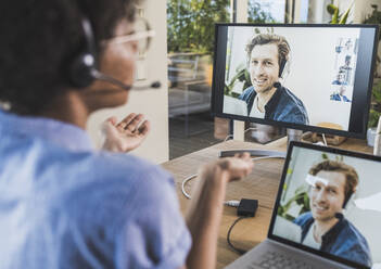 Woman having video conference with man via laptop at home - UUF22487