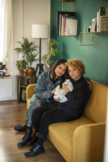 Portrait of lesbian couple sitting together on sofa with pet rabbit - AXHF00059