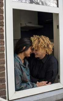 Happy lesbian couple standing together in front of window - AXHF00062