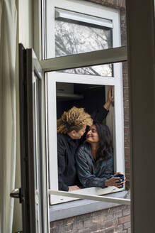 Happy lesbian couple standing together in front of window - AXHF00065
