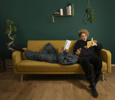 Lesbian couple reading books on sofa - AXHF00068