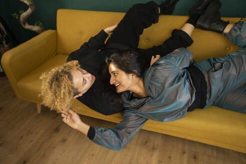 Lesbian couple lying together on sofa - AXHF00077
