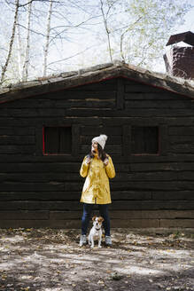 Woman in yellow raincoat standing with dog in front of log cabin - EBBF02099