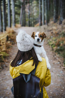 Woman carrying dog in forest - EBBF02111