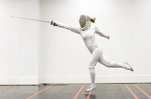 Womanin fencing outfit practicing at gym - JCCMF00711