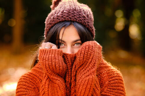 Young female in knitted hat covering face with warm sweater while standing in forest in cold autumn day - ADSF19754