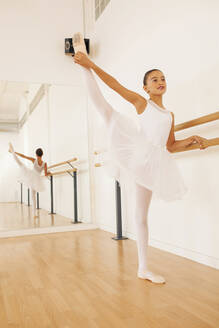 Charming teenage ballerina in pointe shoes stretching legs near ballet barre in dance hall - ADSF19763