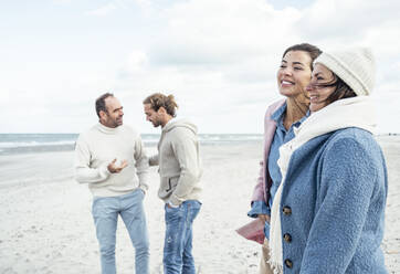 Group of adult friends standing and talking on coastal beach - UUF22553