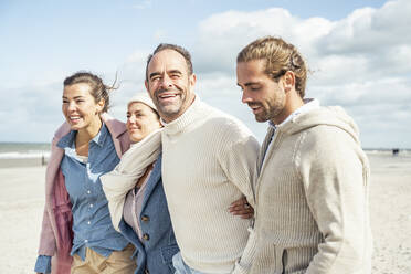 Group of adult friends standing together on coastal beach - UUF22556