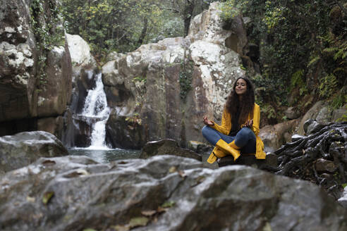 Woman wearing yellow raincoat meditating while sitting on rock against waterfall in forest - KBF00661