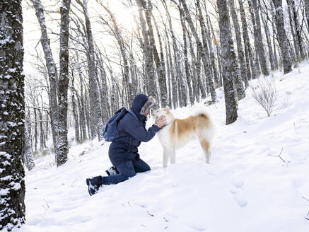 Mid adult man stroking dog while kneeling on snow land in forest - JCCMF00834