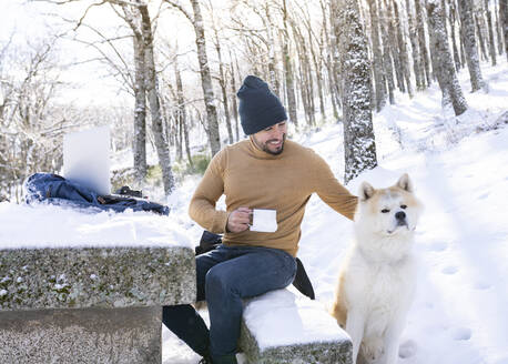 Smiling man holding coffee cup while petting his dog in snowy forest - JCCMF00840