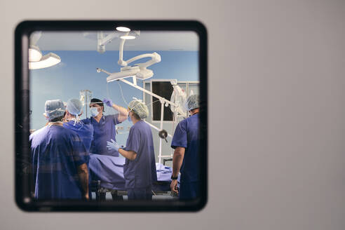 Doctors team wearing face mask working while standing in operation room at hospital - SASF00135