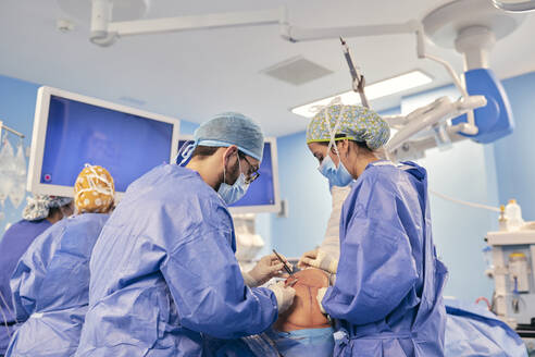 Doctors wearing face mask operating surgery while standing with colleague in background at operation room - SASF00165