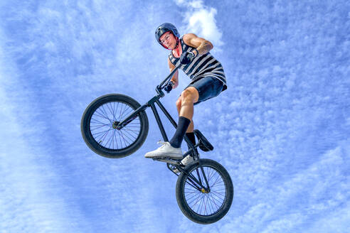 Carefree young man jumping with bicycle against blue sky at bike park - GGGF00789