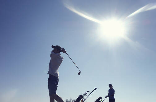 Friends playing golf clear blue sky during sunny day - AJOF00984