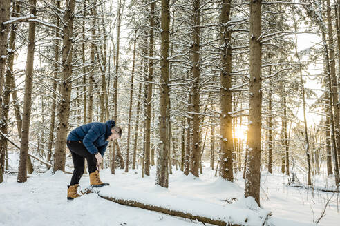 Man wearing warm clothing tying shoelace while standing at pine forest - AWAF00030
