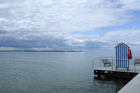 Germany, Schleswig Holstein, Stein, Jetty with blue and white beach cabin on Baltic Sea under cloudy sky - GISF00725