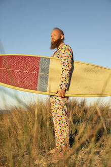 Man in colorful suit with surfboard looking away while standing against sky - KBF00673